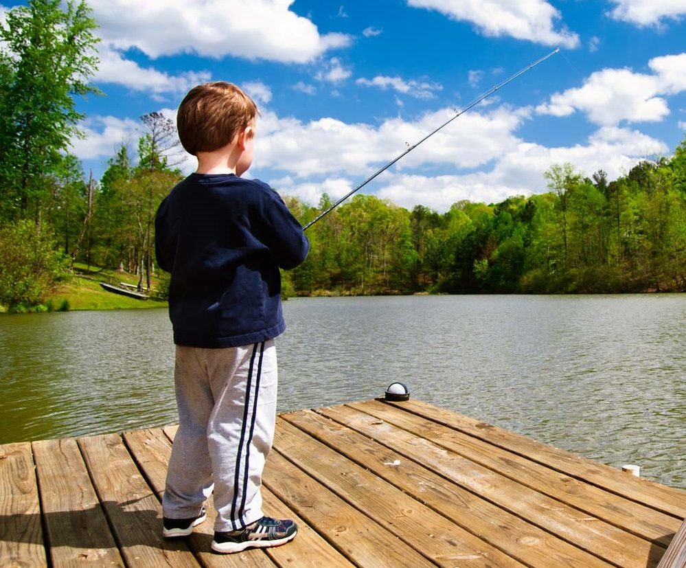 A boy fishing from a dock under a beautiful blue sky
