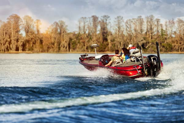 A bass boat makes a hard turn on a sunny lake