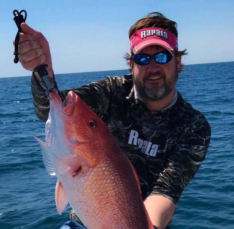 An angler displays a red snapper he has just caught