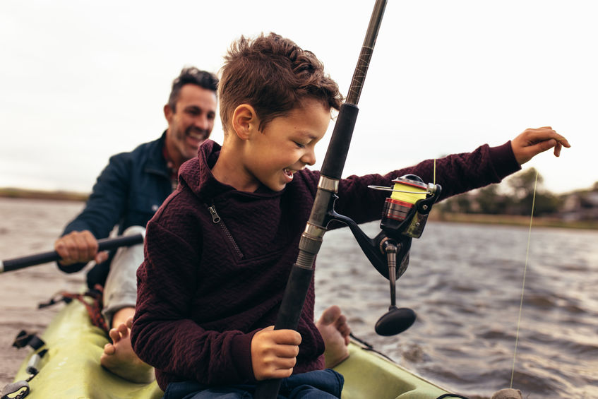 Kid fishing in lake with his father.